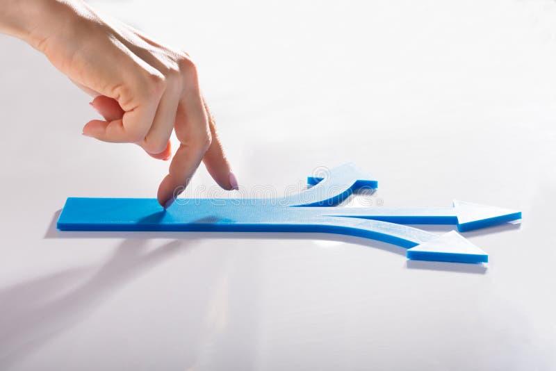 走在蓝色箭头的妇女的手指 免版税库存照片