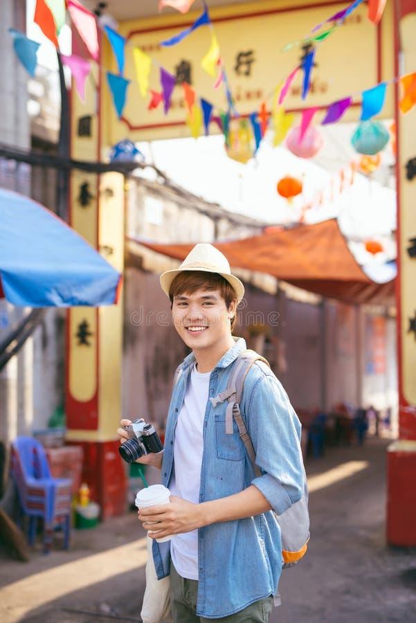 走在街市上的年轻亚洲人旅客购物 免版税库存图片