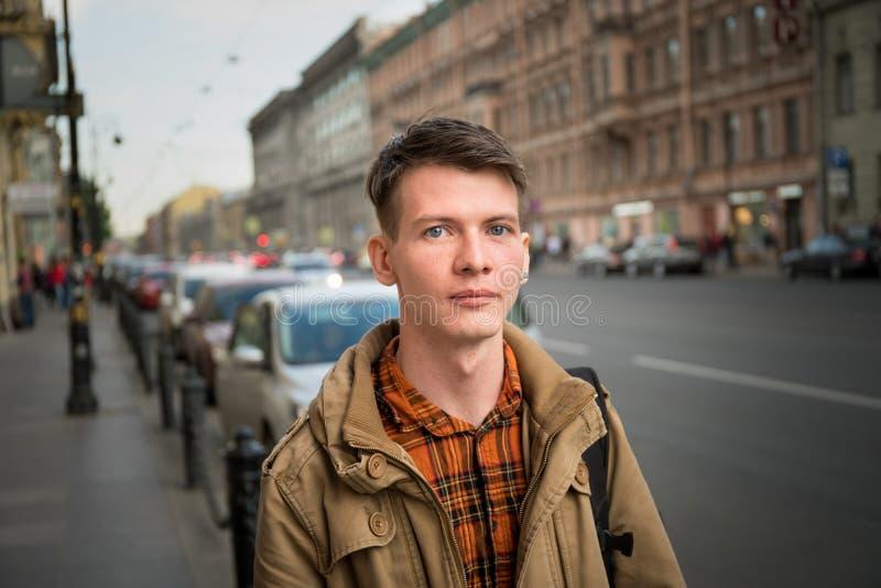 走在街道上和看照相机的英俊的年轻人画象 免版税库存照片