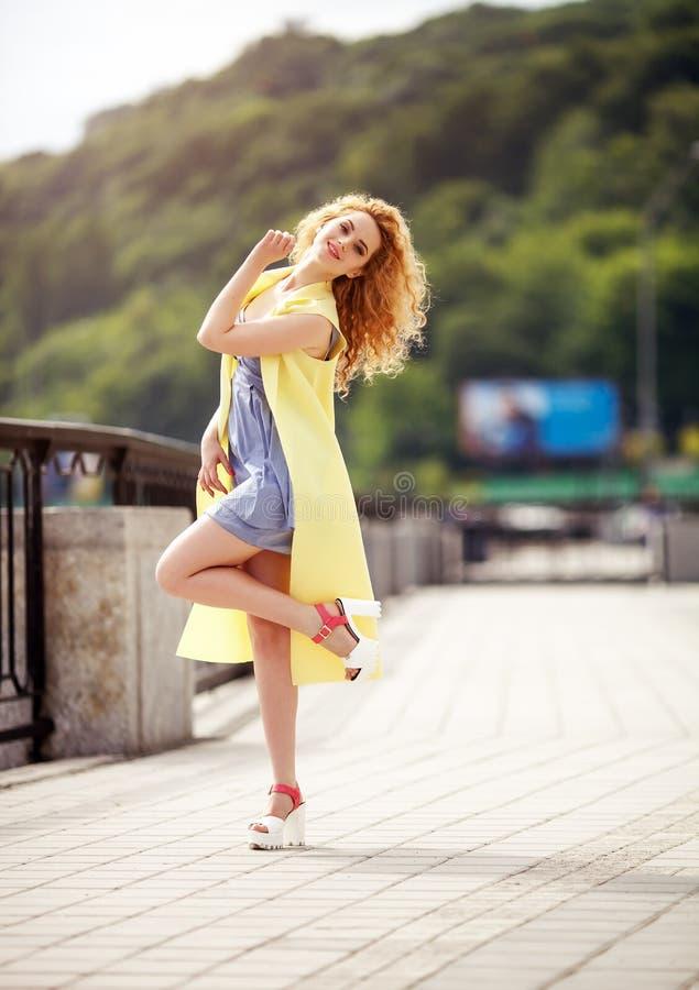 走在街道上的一名年轻美丽的愉快的微笑的妇女的室外画象 式样看的照相机 免版税库存图片