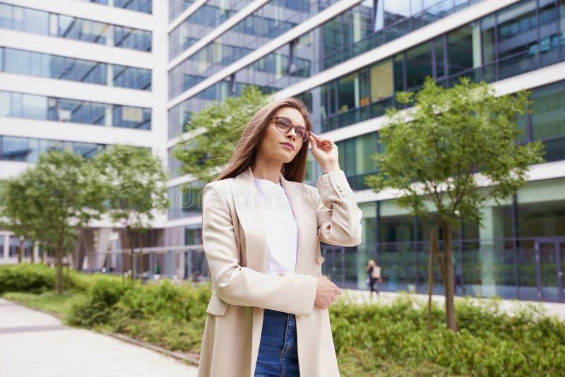 走在街道上的女实业家在办公楼之间 免版税库存照片