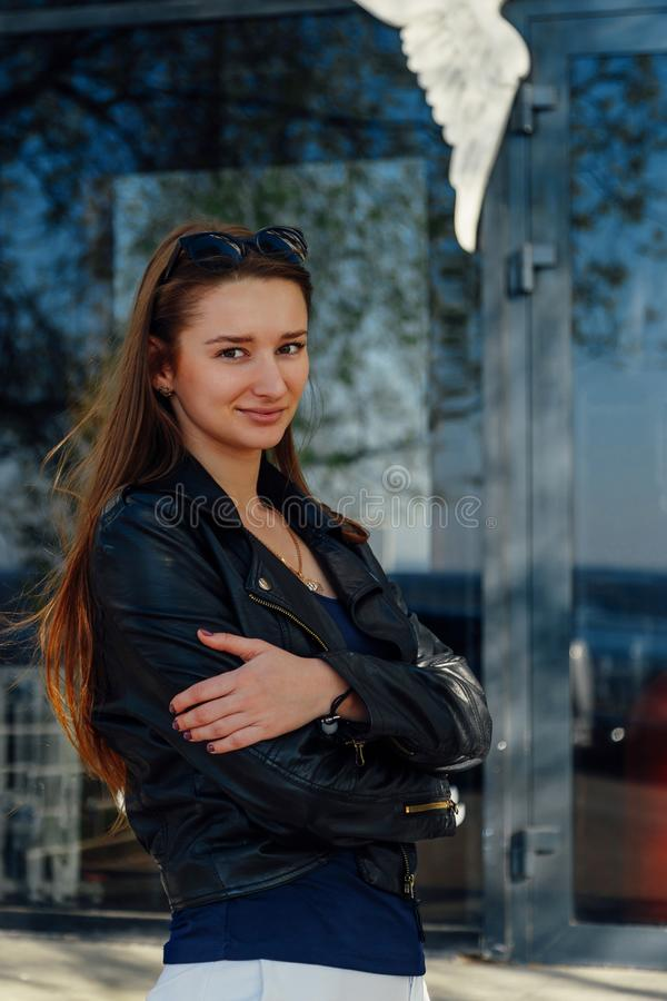 走在街道上的年轻女人 黑皮夹克 图库摄影