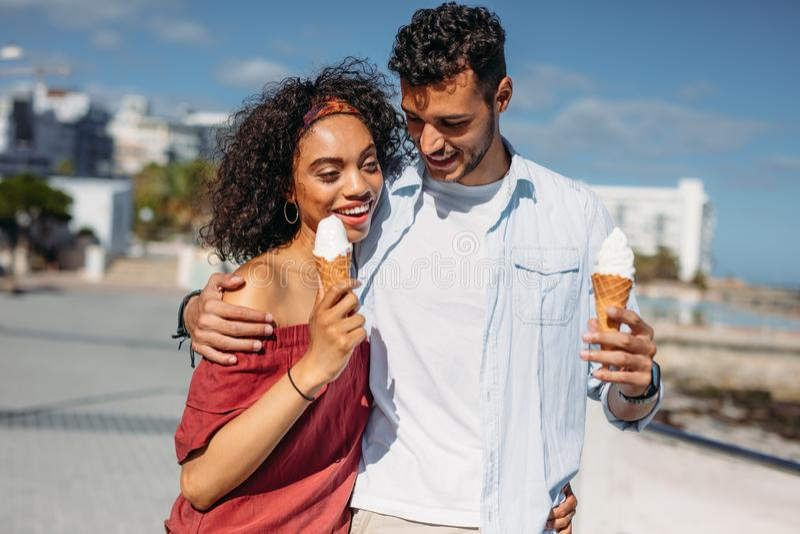 走在街道上的浪漫夫妇吃冰淇淋 免版税图库摄影
