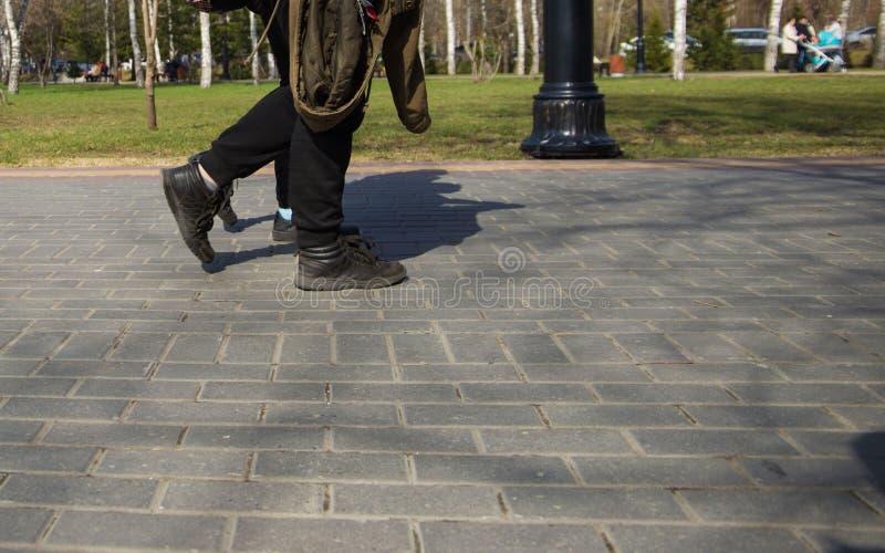 走在街道下的运动鞋的人的脚在一好日子 免版税库存照片