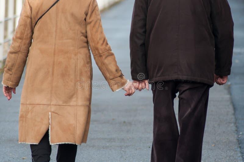 走在街道的资深夫妇握在后面看法的彼此的手指 免版税库存照片