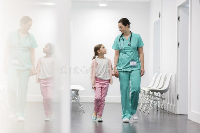 走在走廊的护士和女孩患者在医院 库存图片