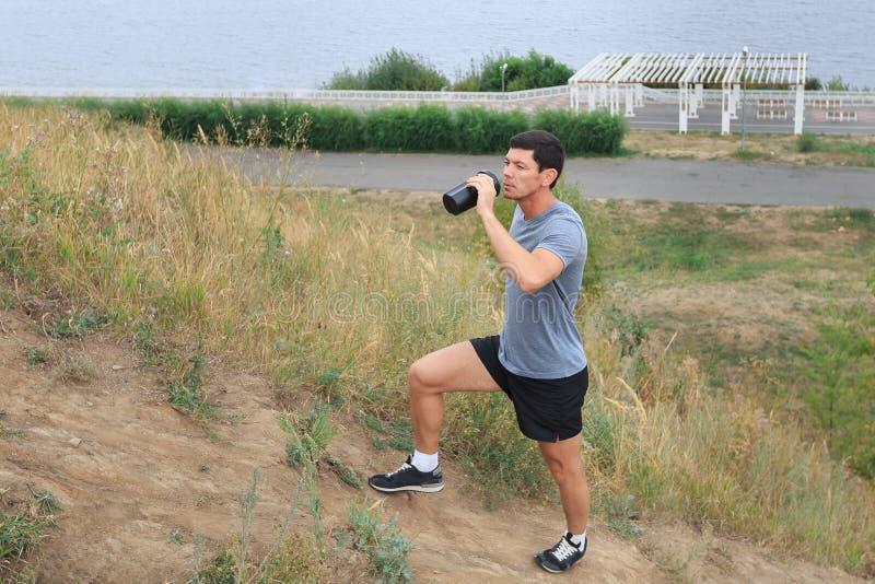 走在足迹的一个年轻人 旅行体育生活方式概念 喝淡水的年轻运动员 免版税库存图片