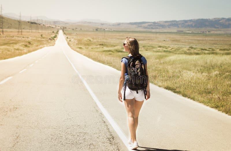 走在路的妇女背包徒步旅行者 库存照片