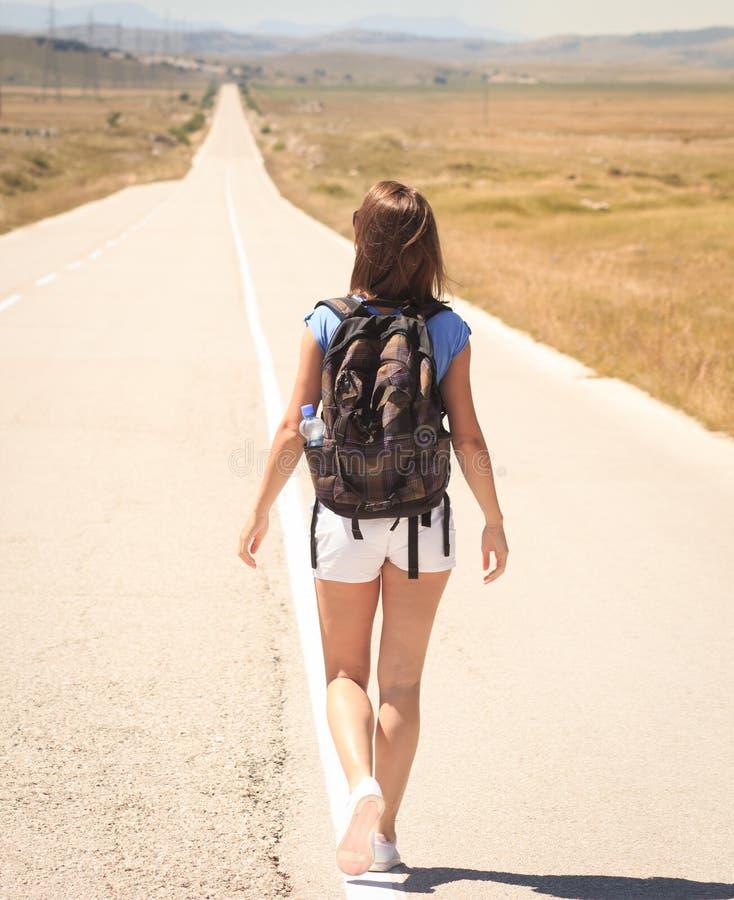 走在路的妇女背包徒步旅行者 免版税库存图片