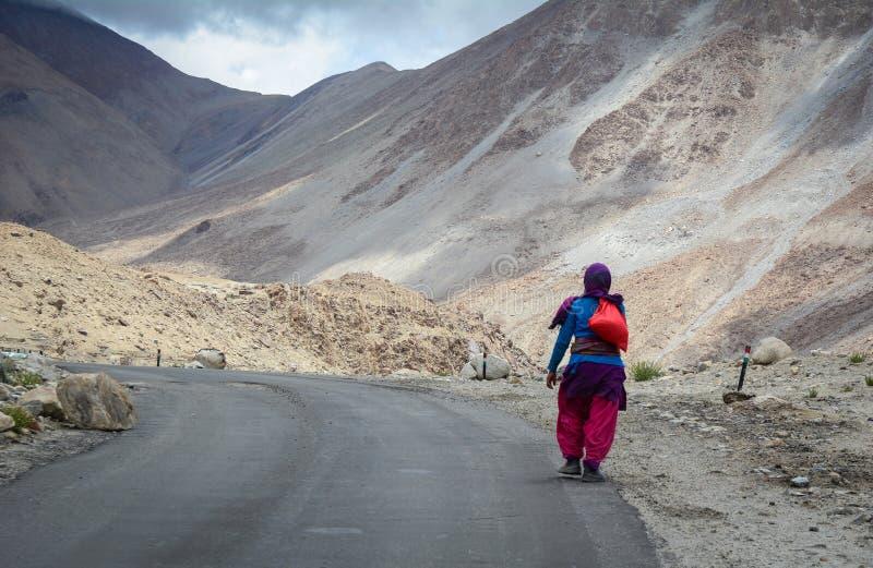 走在路的西藏妇女在Manali,印度 图库摄影