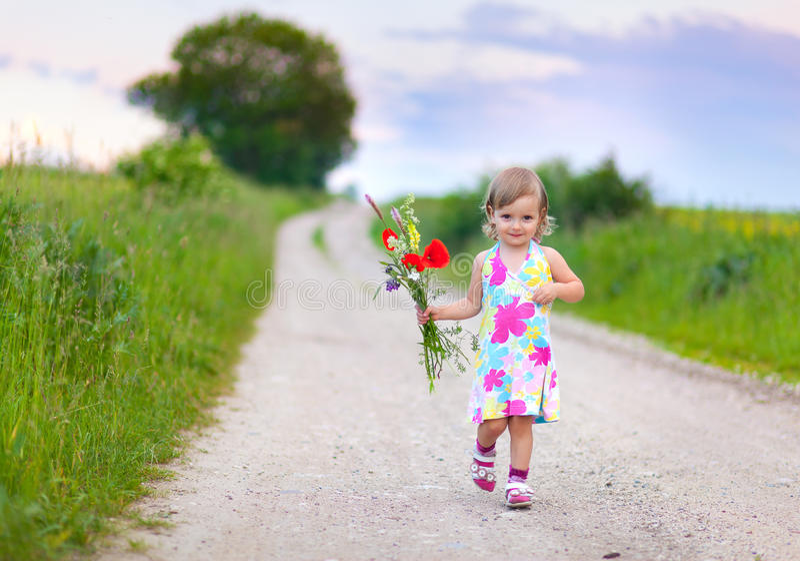 走在路的逗人喜爱的小女孩 免版税库存照片