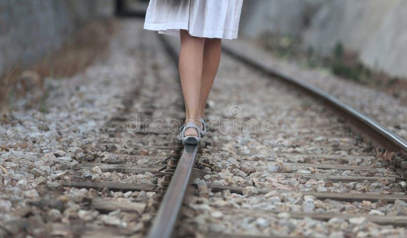 走在路轨道路的女孩 免版税库存图片