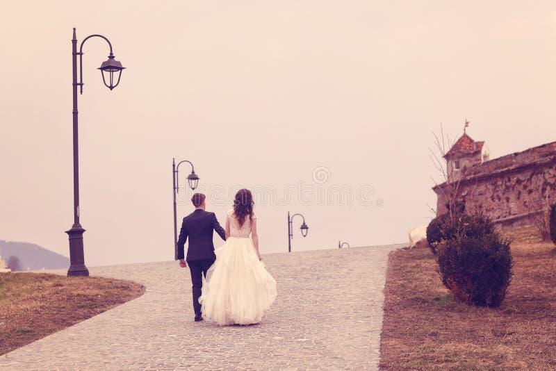 走在路面的新娘和新郎 图库摄影