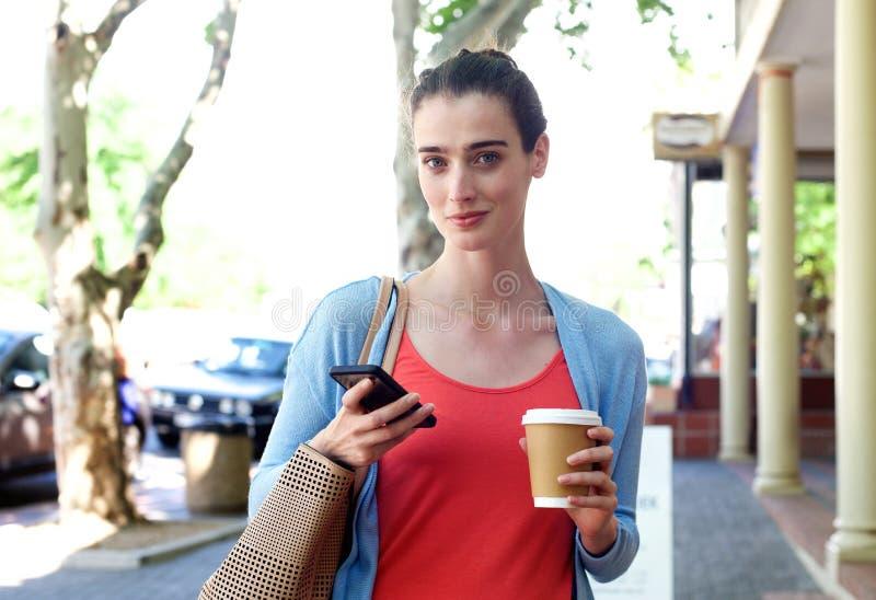 走在边路的妇女拿着手机和咖啡 库存照片