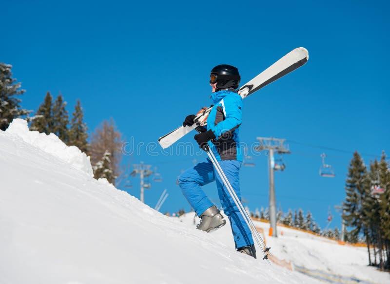 走在运载她的在肩膀的山的倾斜的女子滑雪者滑雪 免版税库存照片