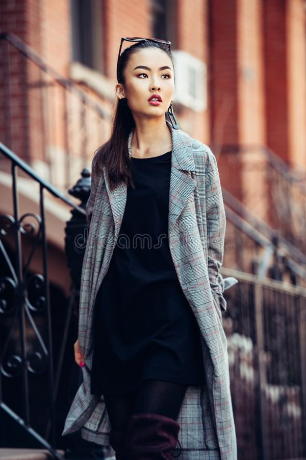 走在都市城市街道上的美丽的亚裔女孩穿流行的服装 图库摄影