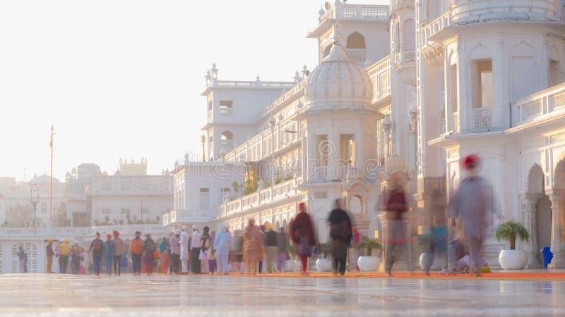 走在金黄寺庙复合体里面的游人和崇拜者在阿姆利则、旁遮普邦、印度、最神圣的象和崇拜plac 库存照片