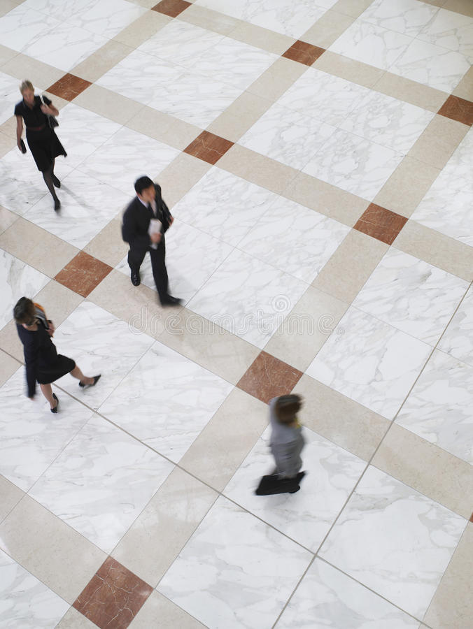 走在铺磁砖的地板上的被弄脏的商人 免版税图库摄影