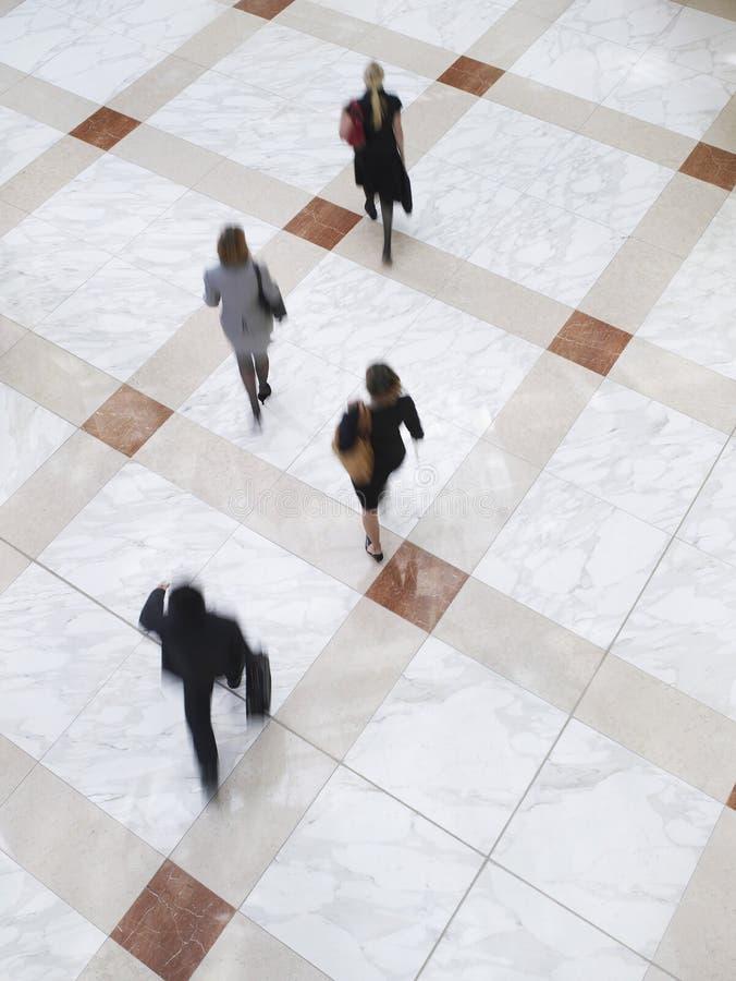 走在铺磁砖的地板上的被弄脏的商人 图库摄影