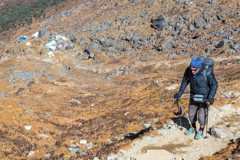 走在陡峭的山行迹的资深人 库存照片
