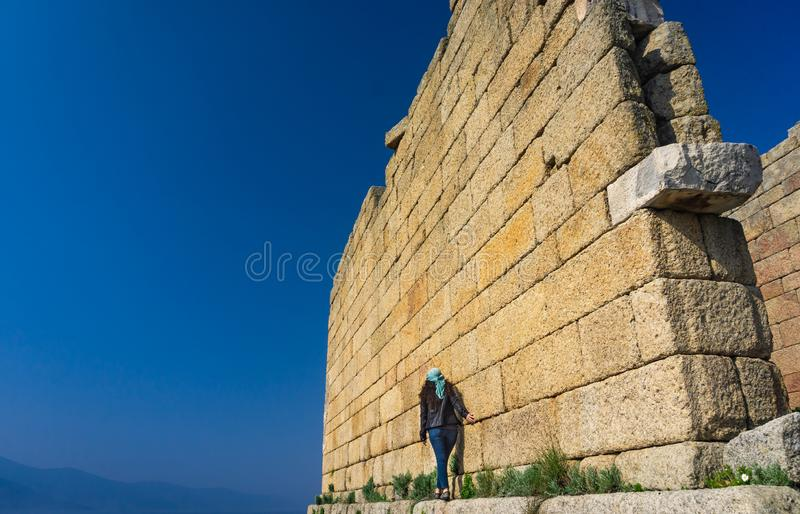 走在雅典娜墙壁附近古庙的女孩  Heracleia古城 米拉斯,艾登,土耳其 r 库存图片
