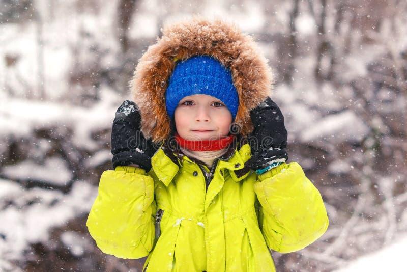 走在雪下的逗人喜爱的小男孩 男孩给愉快的微笑的冬天穿衣 斯诺伊冬天天气 美好的公园冬天 孩子 免版税库存图片