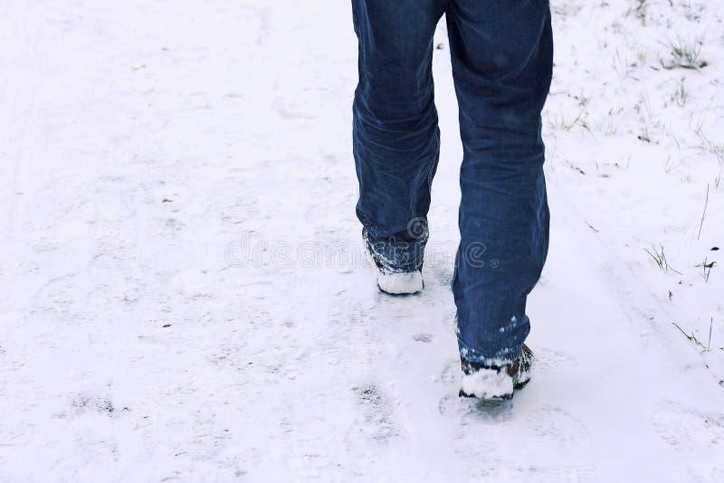 走在雪的一个人的腿 库存照片