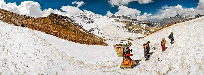 走在雪的人们在尼泊尔 图库摄影
