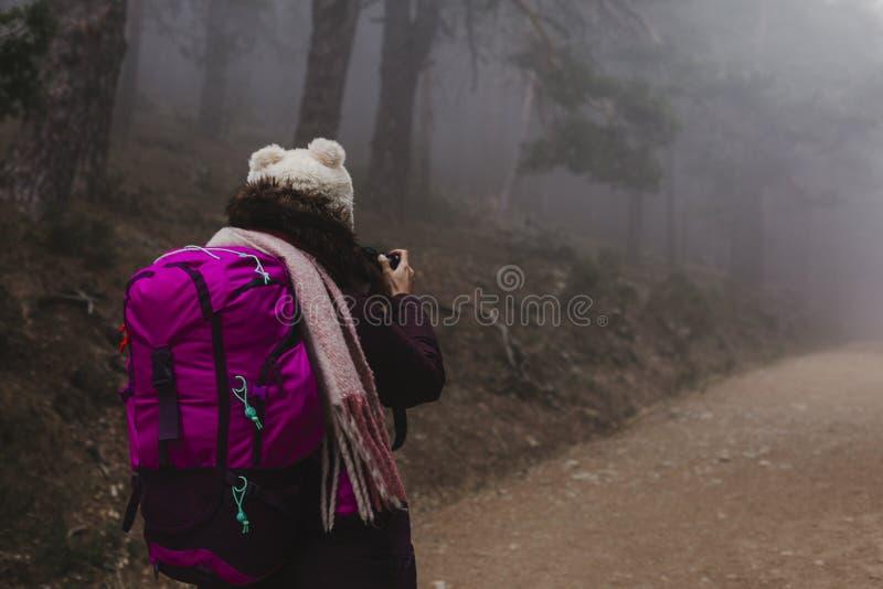 走在雾的成功的徒步旅行者妇女 秋天或冬天季节 库存照片