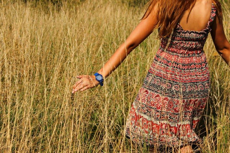 走在领域和奔跑手的年轻美丽的女孩通过高干草夏令时 免版税库存图片