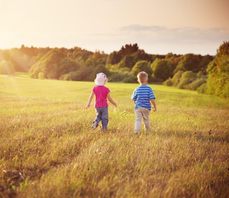 走在领域的男孩和女孩在夏天 库存照片