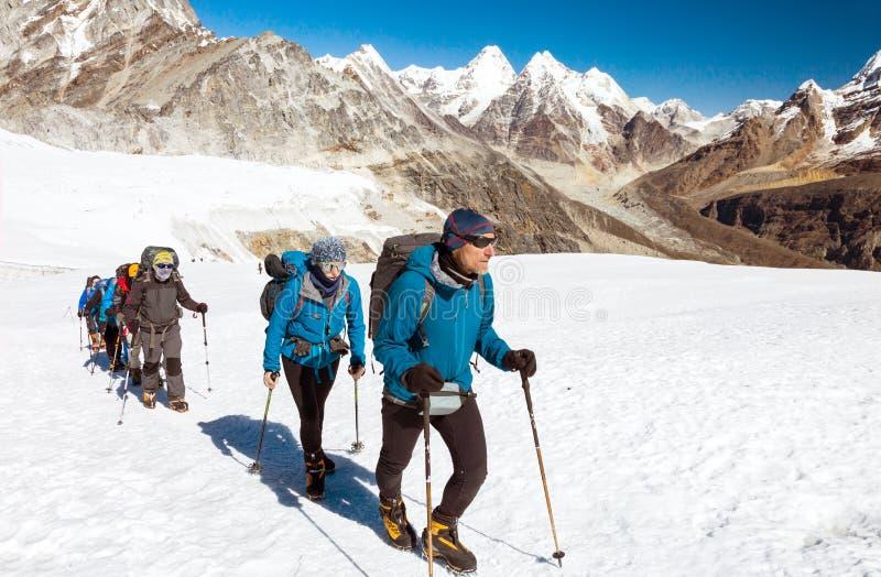 走在高山的冰川的小组登山人 免版税库存照片