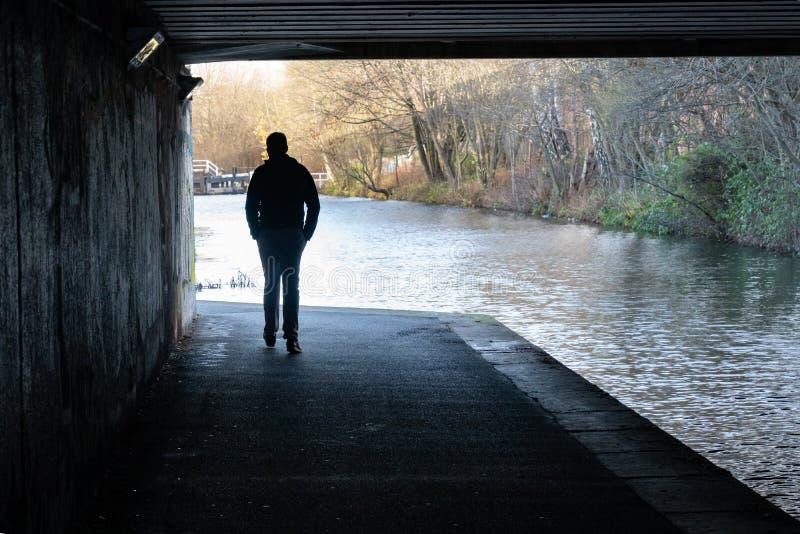 走在高架桥下的一个人的剪影在运河附近 库存图片