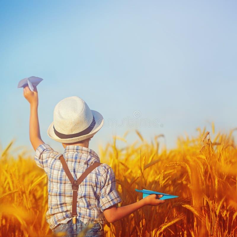 走在麦子金黄领域的逗人喜爱的孩子在一个晴朗的夏日 正方形 图库摄影
