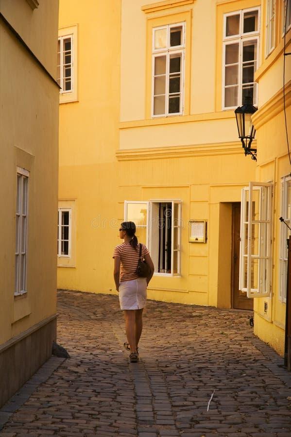 走在黄色大厦之间的女孩 免版税库存图片