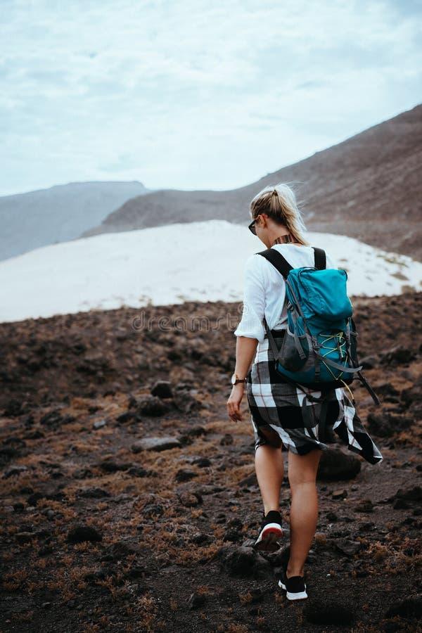 走在黑火山的冰砾和白色沙丘中的贫瘠岩石地形的妇女远足者 圣维森特佛得角 免版税图库摄影