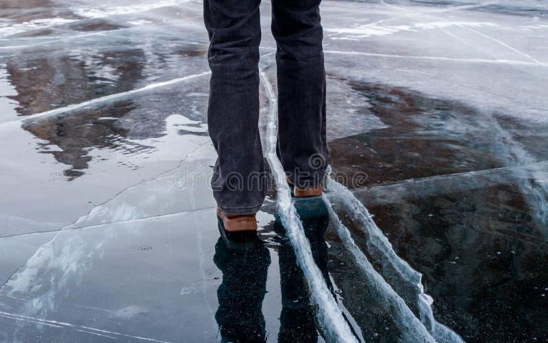 走在冻贝加尔湖蓝色破裂的冰的妇女  库存图片