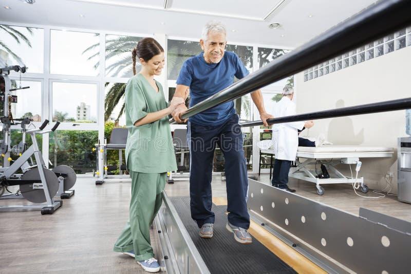 走在巴拉之间的生理治疗师支持的微笑的患者 免版税库存照片