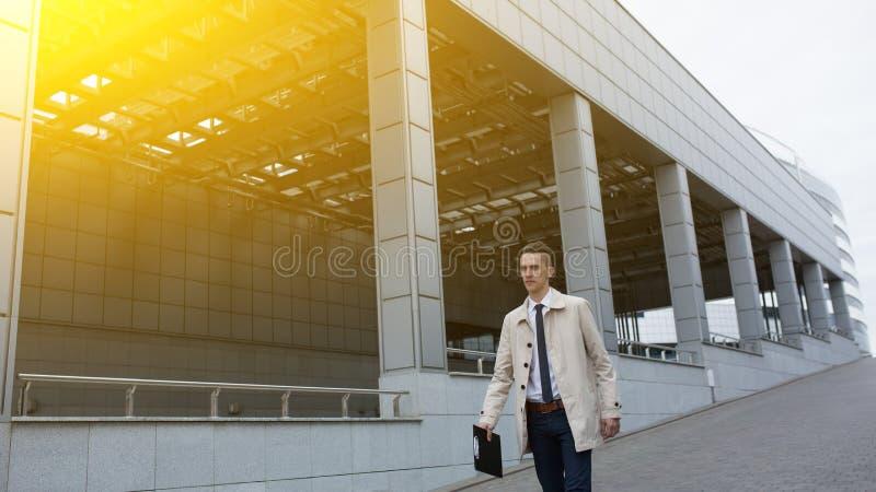 走在财政区的年轻英俊的商人 免版税库存照片