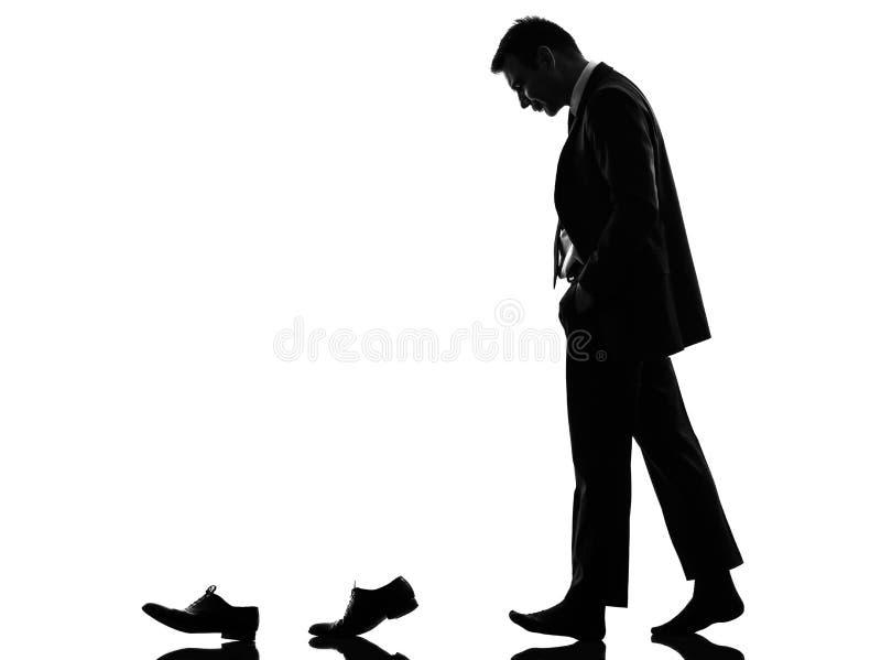 走在他的鞋子后的商人给剪影穿衣 免版税库存图片