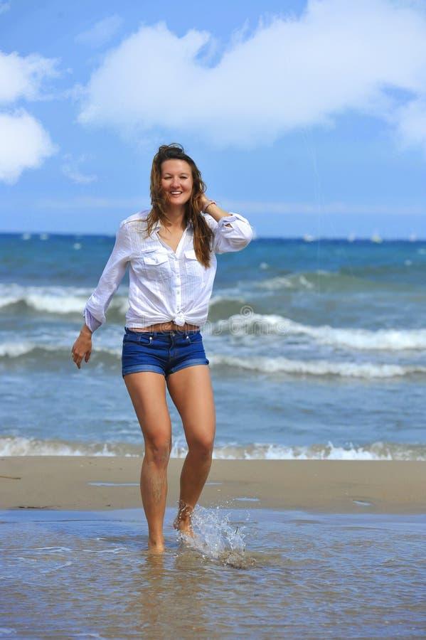 走在水的年轻美丽的女孩在海岸微笑愉快 免版税库存图片