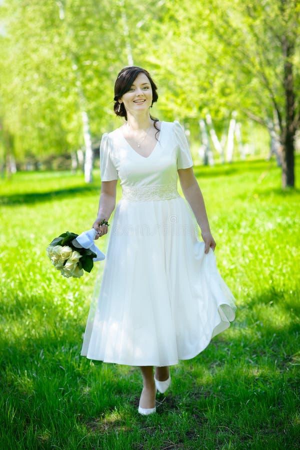 走在绿草的美丽的愉快的新娘 免版税库存图片