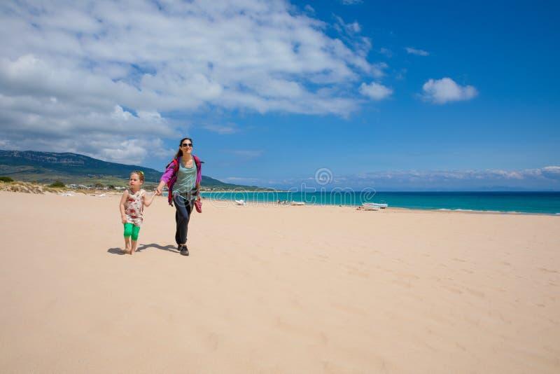 走在Bolonia海滩沙子的母亲和女儿在卡迪士 免版税库存图片