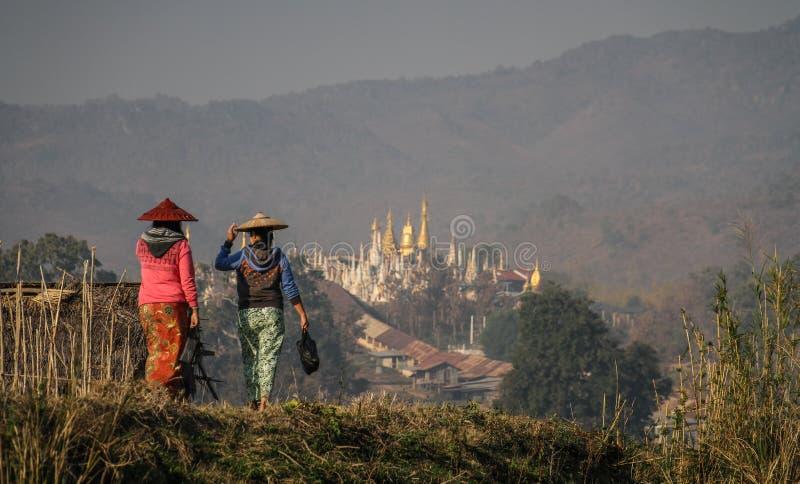 走在Inle湖岸的妇女在与一座塔的Nampan市场上在背景, Inle湖,掸邦,缅甸中 图库摄影