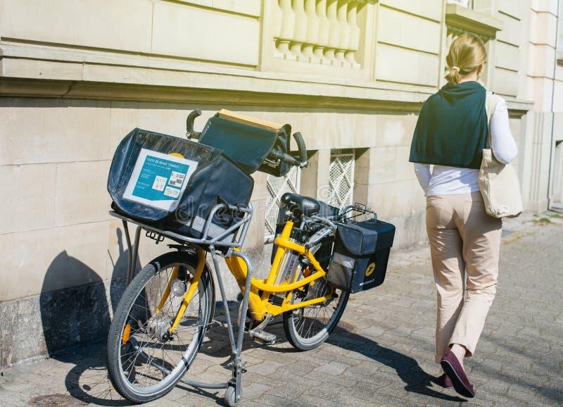 走在La Poste法国bycicle附近的典雅的法国妇女停放 免版税库存图片