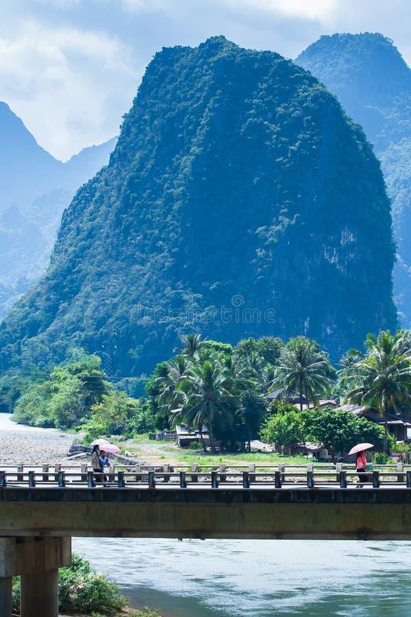 走在Nam歌曲河的老挝人女孩通行证老桥梁,美丽如画的山脉背景 库存照片