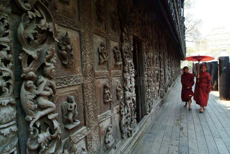 走在Shwenandaw修道院的缅甸年轻修士在曼德勒 免版税库存照片