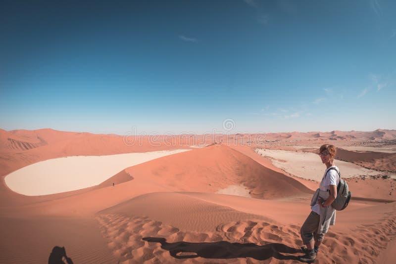 走在Sossusvlei风景沙丘,纳米比亚沙漠, Namib Naukluft国家公园,纳米比亚的游人 下午光 冒险家 免版税库存图片