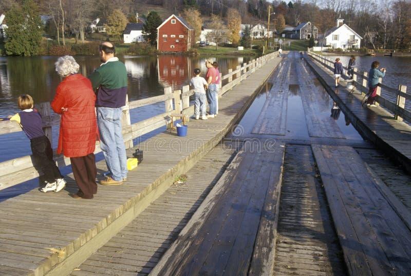走在Sunset湖, Brookfield, VT的Brookfield浮桥的人们 图库摄影