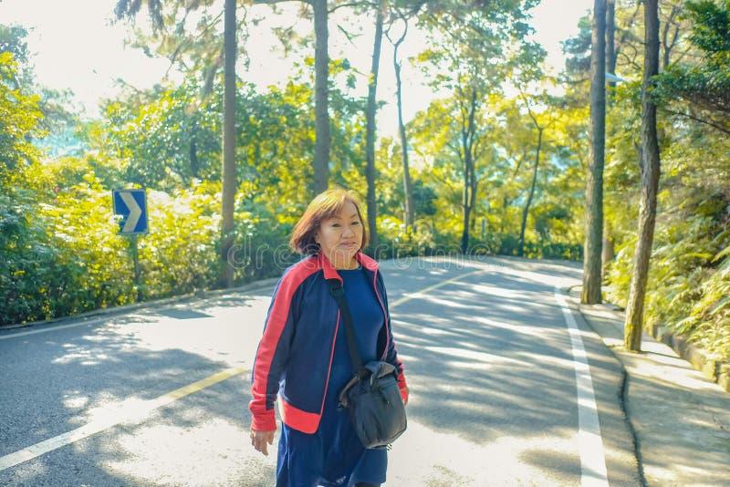 走在xiqiao山公园夫斯汉瓷的美丽的资深亚裔妇女 免版税库存照片